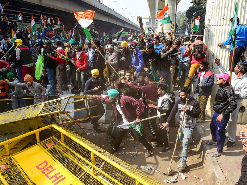 New Delhi: Farmers attempt to break a barricade near Nangloi as they participate in the 'Kisan Gantantra Parade', during their ongoing protest against Centre's farm reform laws, on the occasion of 72nd Republic Day, in New Delhi, Tuesday, Jan. 26,  2021.