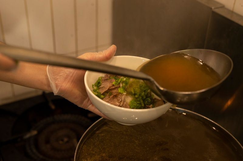 Pour the hot broth over the beef and noodles