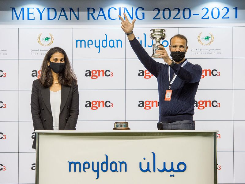 Priya Mathew, Senior Editor for Gulf News, presents Elbashir Salem Elhrari with the trophy for the Agnc3 Handicap