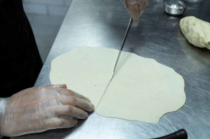 Cut the flattened dough into half.