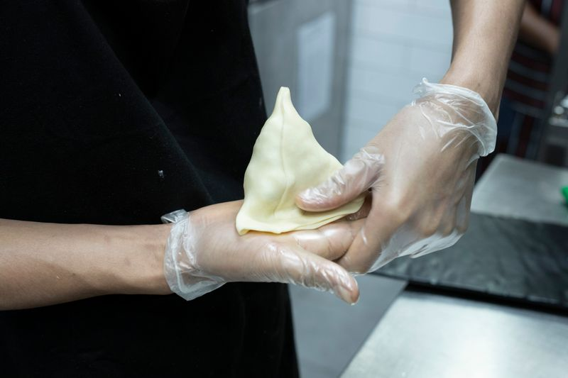Seal, and use a knife to trim off the uneven edges at the base of the samosa.