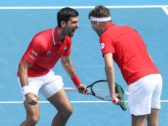 Serbia's Novak Djokovic, left, reacts with partner Filip Krajinovic after winning their ATP Cup match against Canada's Milos Raonic and Denis Shapovalov