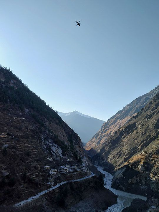 A helicopter conducts an aerial survey after a Himalayan glacier broke and crashed into a dam at Raini Chak Lata village in Chamoli district, northern state of Uttarakhand.