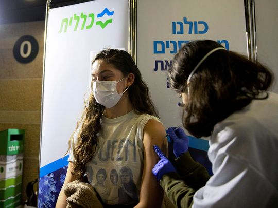 A young woman receives a vaccination against the COVID-19 at a temporary Clalit healthcare maintenance organisation (HMO) centre, at a sports arena in Jerusalem.