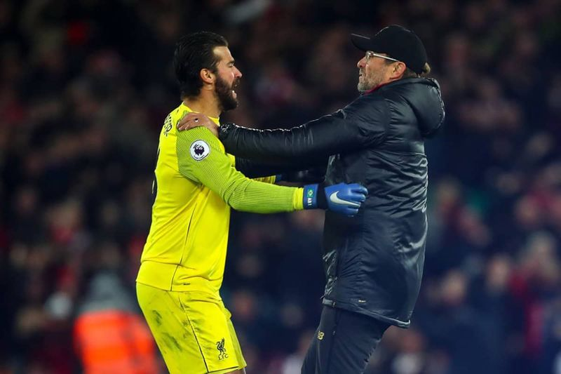 Jurgen Klopp runs onto the pitch to celebrate with Alisson.