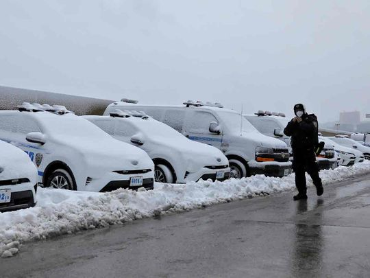An officer from the New York Police Department (NYPD) walks by a row of police vehicles buried in snow near the Hudson Yards precinct in Manhattan, New York City