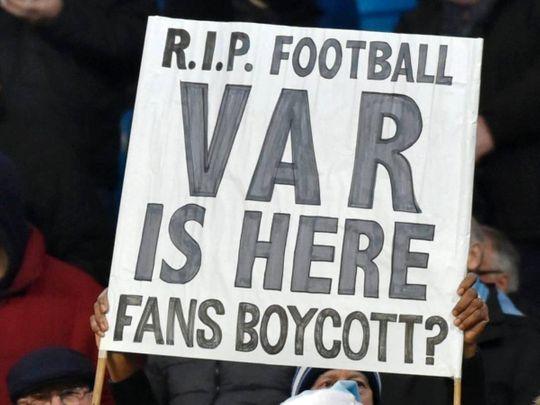 Fans hold up signs protesting against VAR.