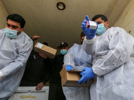 Palestinian workers unload the first shipment of coronavirus vaccines, in the southern Gaza Strip February February 17, 2021.