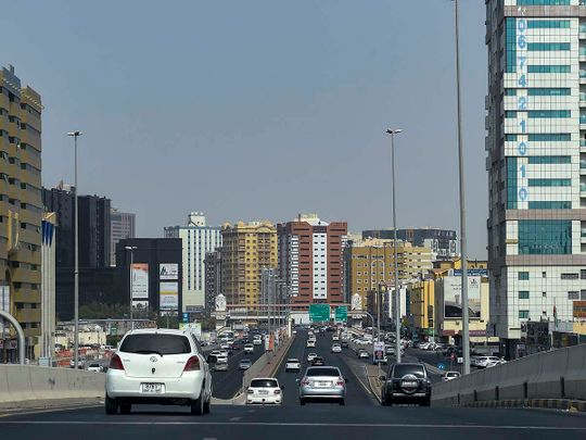 Stock Ajman skyline taxi bus street
