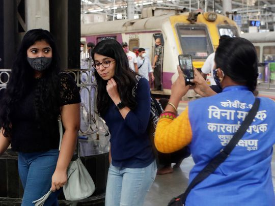 A municipal worker takes visual evidence of a commuter not wearing a face mask in order to give her a penalty at Chhatrapati Shivaji Maharaj Terminus in Mumbai, on February 20, 2021.