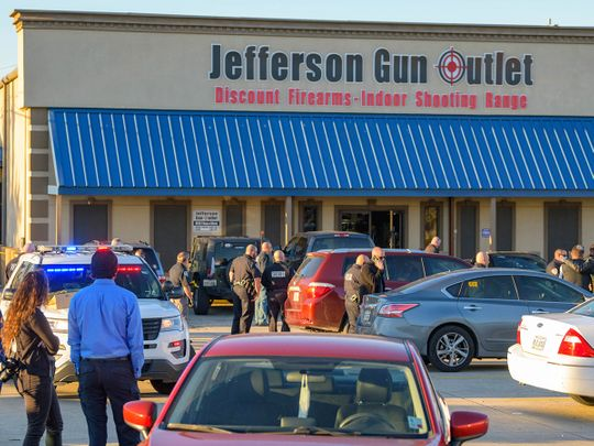 Bystanders react at the scene of a multiple fatality shooting at the Jefferson Gun Outlet in Metairie.