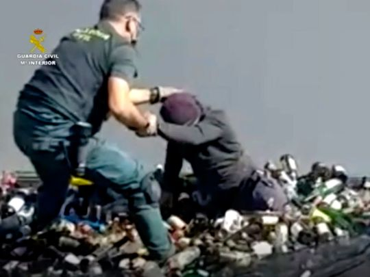 An officer of the Guardia Civil helps a man out from under glass bottles in a container in Melilla.