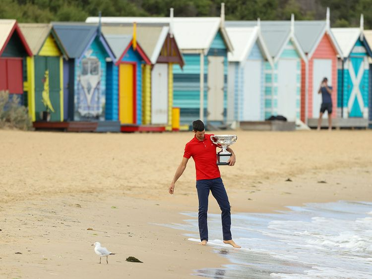 Novak Djokovic on Brighton Beach in Melbourne with the Australian Open trophy