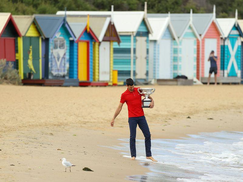 Novak Djokovic on Brighton Beach in Melbourne with the Australian Open trophy