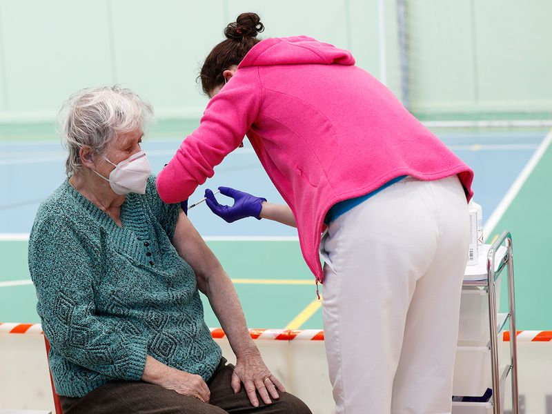 An elderly woman receives Moderna COVID-19 vaccine at a sports hall in Ricany, Czech Republic.