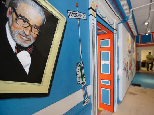 In this May 4, 2017, file photo, a mural that features Theodor Seuss Geisel, left, also know by his pen name Dr. Seuss, covers part of a wall near an entrance at The Amazing World of Dr. Seuss Museum, in Springfield, Mass.