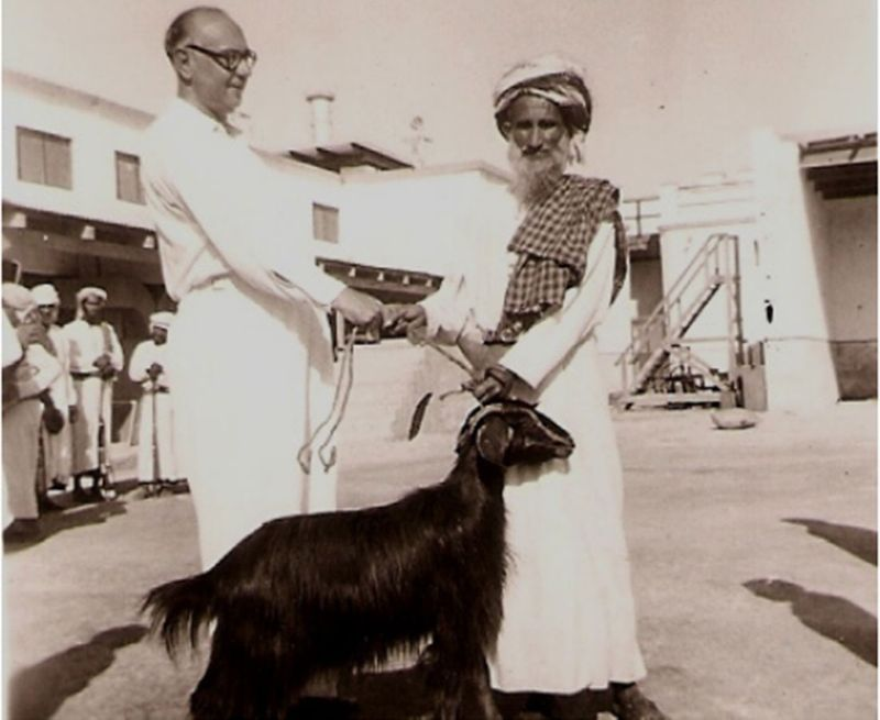 Harold Dunn with a visiting Shaikh bearing a gift, in the courtyard. (photo: Dunn, 1952- 53)