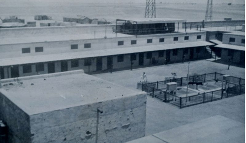 The rest house wing with shaded sitting- area above. The garage (left) and the Met. stations (with two stevenson screens) occupy much of the courtyard. In the background, building of RAF Sharjah. (Photo: Adams, 1940-41).