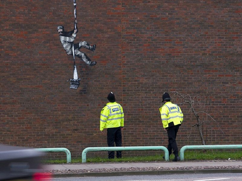 Police officers look at the mural of artist Banksy on a wall at HM Reading Prison in Reading, Britain in this picture obtained from the artist's official Instagram account. @banksy/banksy.co.uk via REUTERS THIS IMAGE HAS BEEN SUPPLIED BY A THIRD PARTY. MANDATORY CREDIT. NO RESALES. NO ARCHIVES.