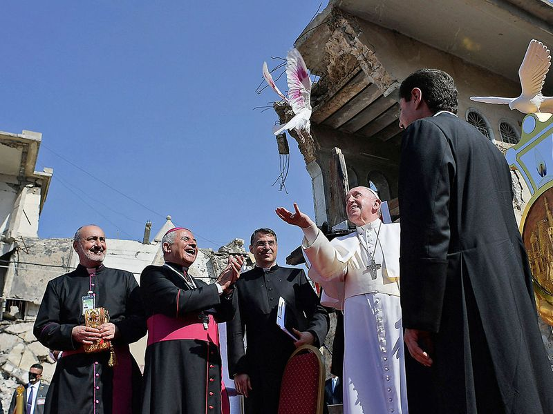 A handout picture released by the Vatican media office, shows Pope Francis, releasing a white dove at a square near the ruins of the Syriac Catholic Church of the Immaculate Conception (al-Tahira-l-Kubra), in the old city of Iraq's northern Mosul.