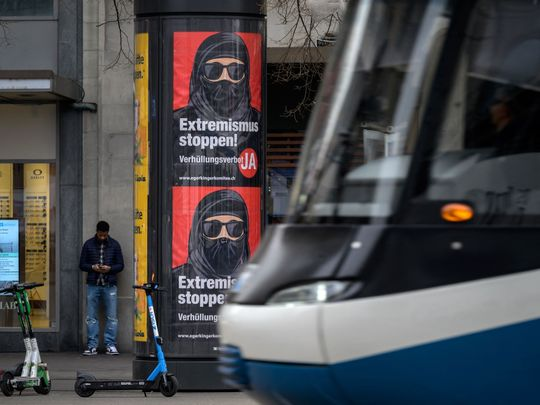 A tram passes by campaign posters, in favour of the