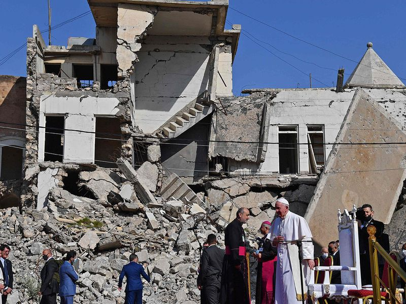 Pope Francis (C), looks on at the ruins of the Syriac Catholic Church of the Immaculate Conception (al-Tahira-l-Kubra), in the northern city of Mosul on March 7, 2021. - Pope Francis, on his historic Iraq tour, visits today Christian communities that endured the brutality of the Islamic State group until the jihadists'