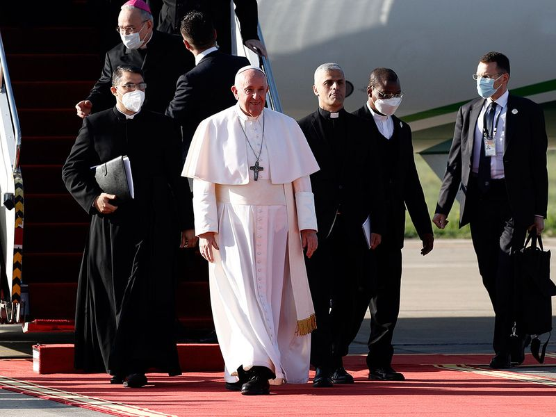 Pope Francis, center, arrives at the Irbil international airport, Iraq, Sunday, March 7, 2021. Pope Francis arrived in northern Iraq on Sunday, where he planned to pray in the ruins of churches damaged or destroyed by Islamic State extremists and celebrate an open-air Mass on the last day of the first-ever papal visit to the country.  (AP Photo/Hadi Mizban)