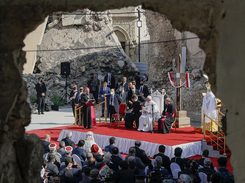 Pope Francis, listens to Mosul and Aqra Archbishop Najib Mikhael Moussa during a gathering to pray for the victims of war at Hosh al-Bieaa Church Square, in Mosul, Iraq, once the de-facto capital of IS, Sunday, March 7, 2021.