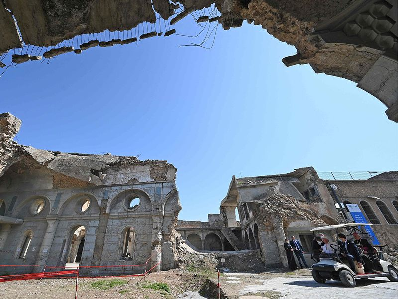 Pope Francis rides in a golf cart at the ruins of the Syriac Catholic Church of the Immaculate Conception (al-Tahira-l-Kubra), in the old city of Iraq's northern Mosul on March 7, 2021.