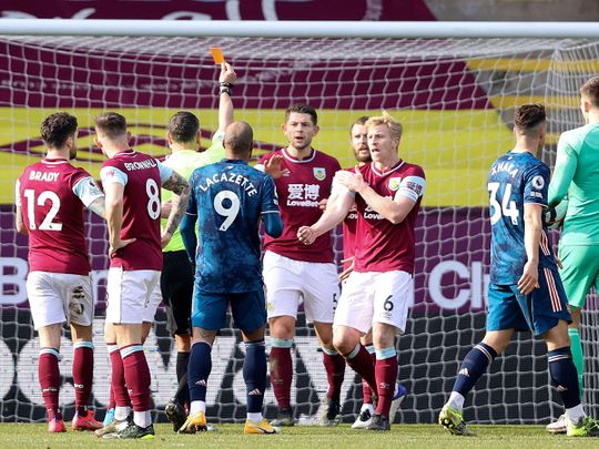 Referee Andre Marriner initially shows a red card for handball to send off Burnley's Dutch defender Erik Pieters, a decision that was reversed after VAR review
