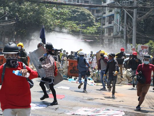 Protesters are dispersed as police fire tear gas during a demonstration in Yangon, on March 8, 2021.