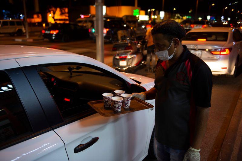 A waiter serves Dh1 karak chai to customers waiting in cars outside the Al Farwania restaurant.