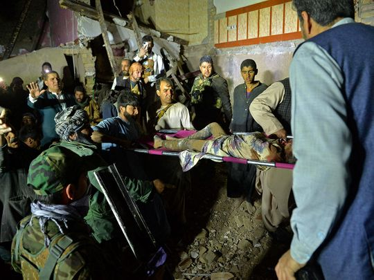Rescuers carry an injured girl amid the debris of a damaged house after a car bomb blast in Herat.