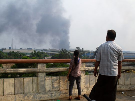 People look at smoke believed to be from a factory fire during the security force crack down on anti-coup protesters at Hlaingthaya, Yangon.