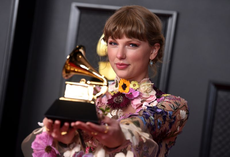 Taylor Swift stands in the press room receiving this year's Album of the Year award