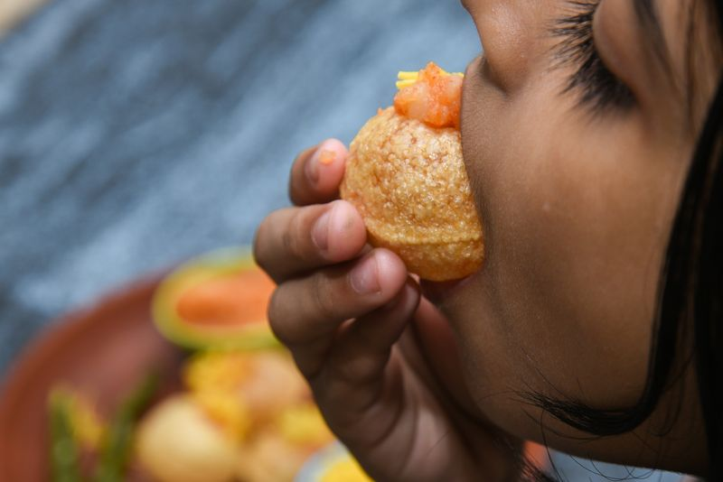 The only right way to eat a pani puri is to pop an entire puri, fillings and all, into your mouth.