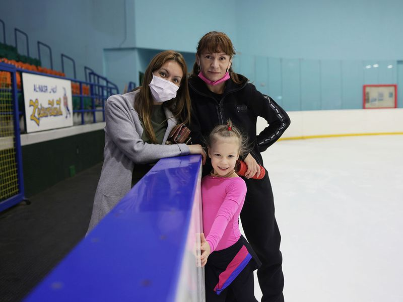 Young ice-skater Lyudmila Zykova with mother Tanya and coach Svetlana Volkova