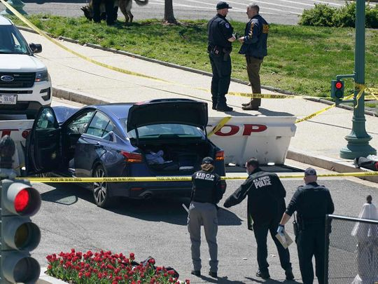 U.S. Capitol Police officers stand near a car that crashed into a barrier on Capitol Hill in Washington, Friday, April 2, 2021