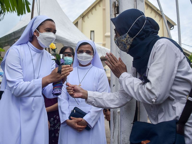 A Muslim group gathers at the gates of a cathedral in Makassar to wish the nuns and show goodwill at Easter on April 4, 2021, following the March 28 suicide bombing at the cathedral on Palm Sunday in Indonesia