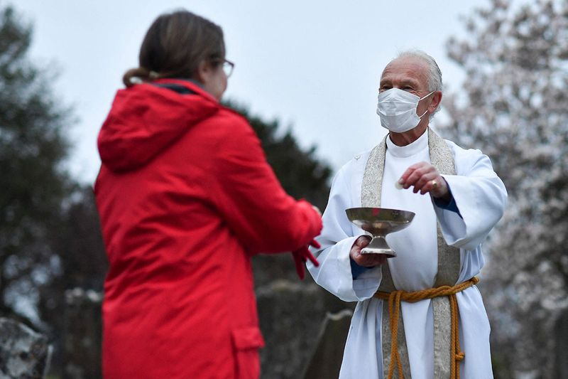 The vicar of Brenchley, Reverend Campbell Paget (R) conducts an Easter Service at dawn in the churchyard of All Saints' Church in Brenchley in south east England on Easter Sunday, April 4, 2021, adhering to government advice on social distancing during the coronavirus pandemic.