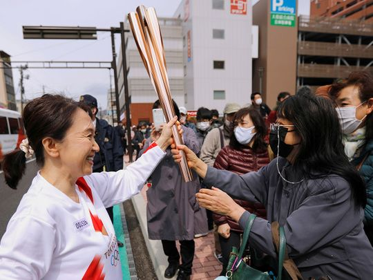 Spectators try to touch the torch carried by torchbearer Junko Ito, after her run during the Tokyo 2020 Olympic torch relay on the second day of the relay in Fukushima