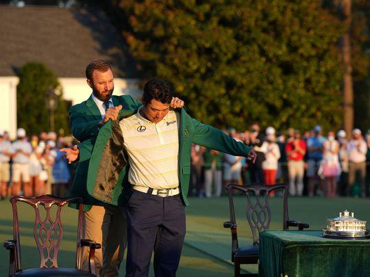 Dustin Johnson, left, the 2020 Masters Tournament champion, helps Hideki Matsuyama put on his green jacket after winning the 2021 Masters Tournament at Augusta National