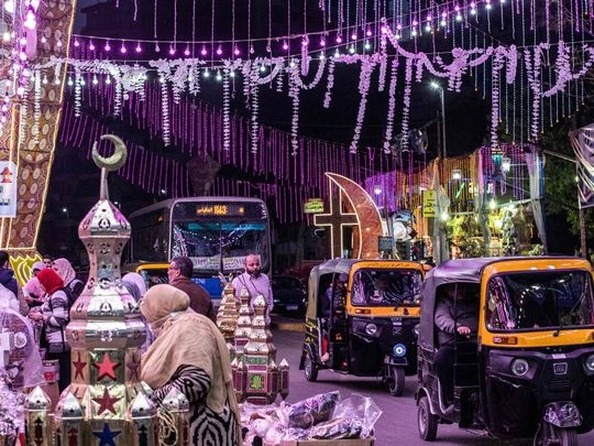 Tuk-tuks (motorised rickshaws) drive past a stall selling Ramadan lanterns along a main street in the in the northern suburb of Shubra (home to a large Christian population) of Egypt's capital Cairo on April 12, 2021, at the start of the Muslim holy fasting month of Ramadan.