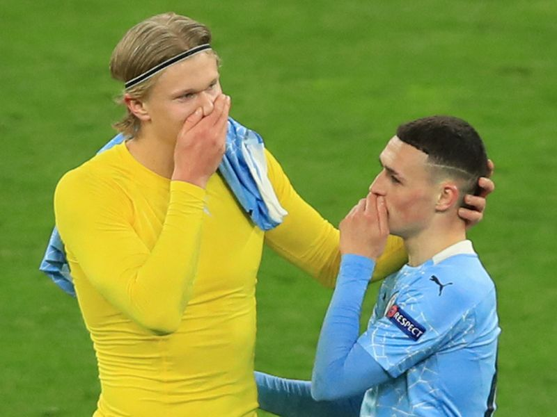 Dortmund's Norwegian forward Erling Braut Haaland (L) and Manchester City's English midfielder Phil Foden speak after the UEFA Champions League quarter-final second leg football match between BVB Borussia Dortmund and Manchester City in Dortmund, western Germany, on April 14, 2021. (Photo by WOLFGANG RATTAY / various sources / AFP)
