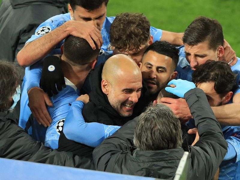 TOPSHOT - Manchester City's English midfielder Phil Foden (C, hidden) celebrates scoring the 1-2 goal with his team-mates and Manchester City's Spanish manager Pep Guardiola during the UEFA Champions League quarter-final second leg football match between BVB Borussia Dortmund and Manchester City in Dortmund, western Germany, on April 14, 2021. (Photo by WOLFGANG RATTAY / various sources / AFP)