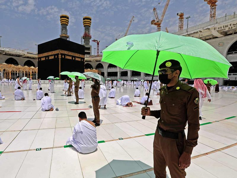 Members of the Saudi security forces holding umbrellas stand guard, as worshippers pray around the Kaaba in the Grand mosque complex in the Saudi city of Mecca, during the Friday prayers of the Muslim holy fasting month of Ramadan, on April 16, 2021.