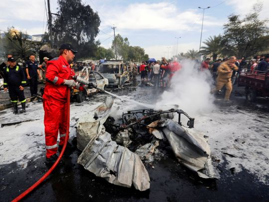 A firefighter inspects the site of a car bomb attack in Sadr City district of Baghdad, Iraq April 15, 2021.