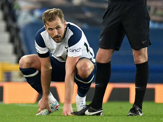 Tottenham Hotspur striker Harry Kane holds his foot before leaving the pitch injured against Everton