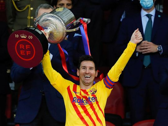 FC Barcelona's Lionel Messi celebrates winning the Copa del Rey with the trophy.