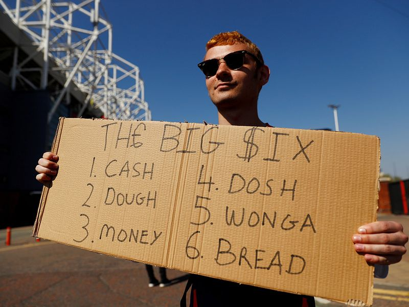 A fan holds up a sign with six different names for money as a reference to the 'big six' teams that joined the European Super League from the English Premier League.